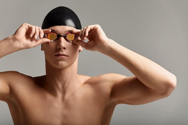 Giovane nuotatore maschio che si prepara per l'inizio, ritratto ravvicinato di un nuotatore in maschera e cappello, sfondo grigio, spazio copia, concetto di nuoto.