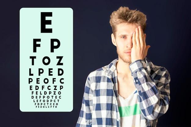 Giovane maschio prova la vista dell'occhio e copre l'occhio con la mano b