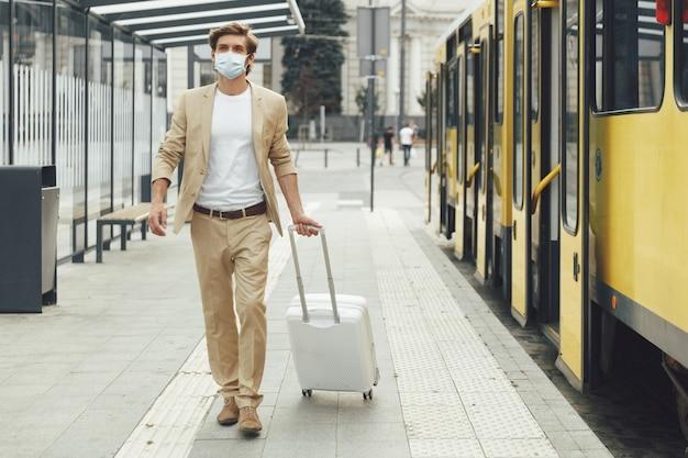 Giovane turista maschio vestito in abito formale e mascherina medica che trasportano bagagli alla fermata del tram