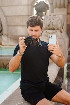 Giovane turista maschio che fotografa sulla fotocamera e sullo smartphone mentre è seduto vicino alla fontana