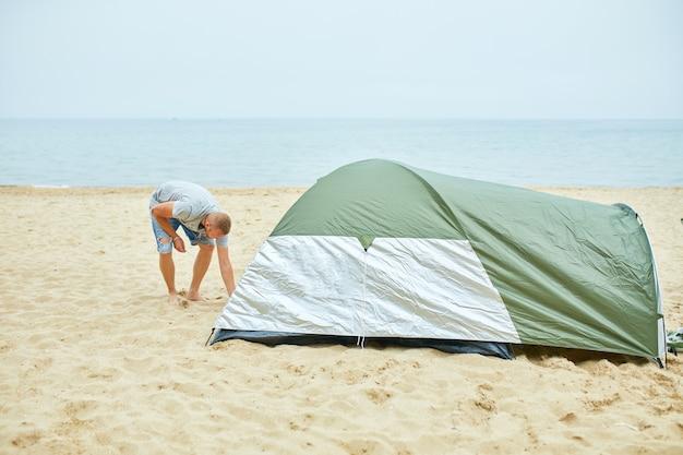 Il giovane turista maschio mette una tenda verde nella costa della spiaggia. l'uomo allestisce un campo per un'escursione, raccoglie una tenda da solo, nuovo viaggio normale.