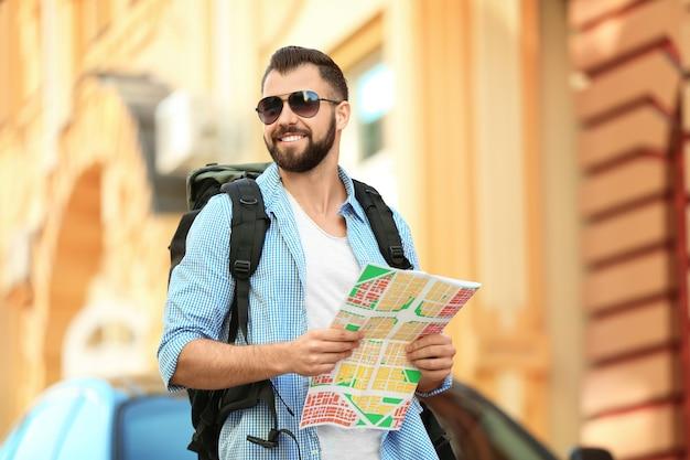 Giovane turista maschio con mappa sulla strada