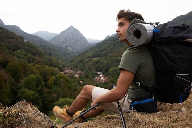 Giovane viaggiatore maschio che fa un'escursione da solo con lo spazio della copia