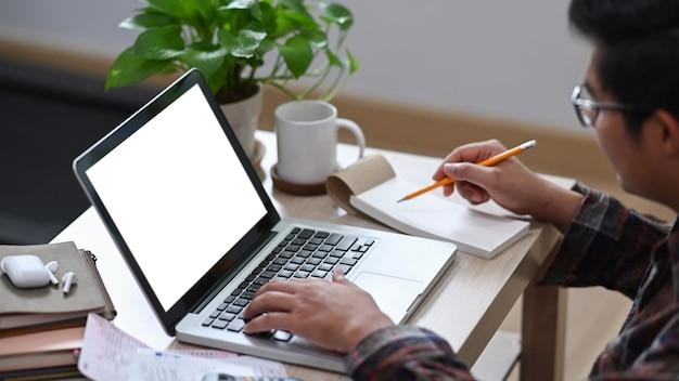 Giovane maschio utilizzando laptop e controllando l'equilibrio e i costi in soggiorno.