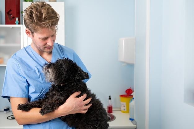 Giovane medico veterinario maschio con lo stetoscopio che tiene e che esamina il cane sveglio alla clinica veterinaria. assistenza sanitaria per animali domestici e concetto medico.