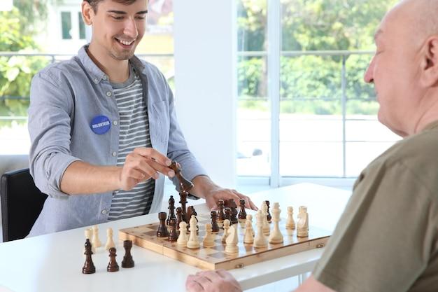 Giovane volontario maschio che gioca a scacchi con un uomo anziano nella stanza luminosa