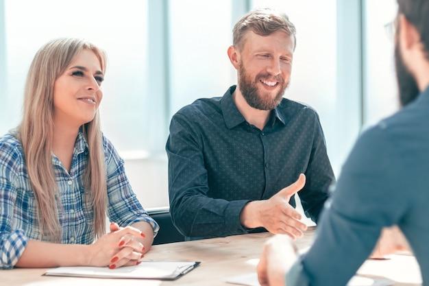 Giovane che risponde alle domande dei manager durante un colloquio. il concetto di occupazione