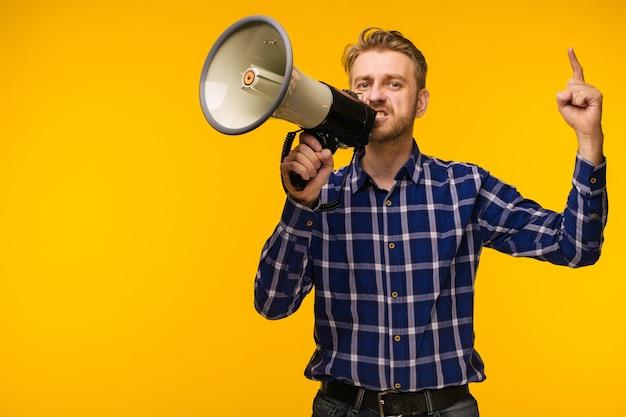 Il giovane come appassionato di calcio con il megafono isolato su studio arancione - immagine