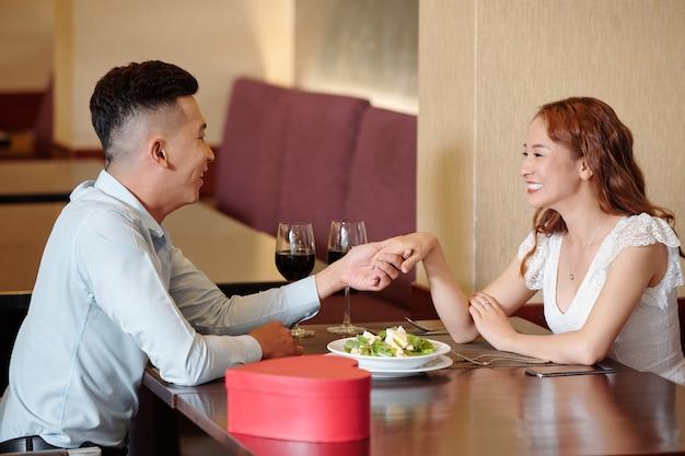 Giovane che chiede alla ragazza di dargli una mano quando sono seduti al tavolo del ristorante
