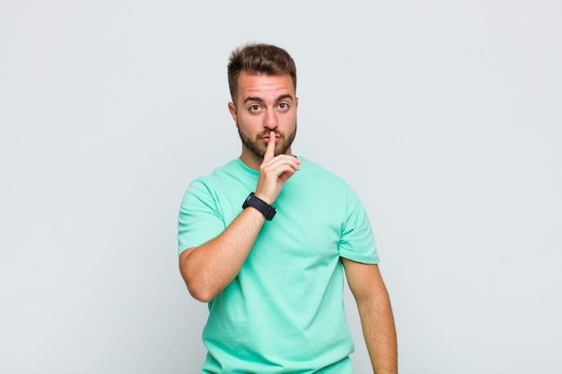 Giovane che chiede silenzio e silenzio, gesticolando con il dito davanti alla bocca, dicendo shh o mantenendo un segreto
