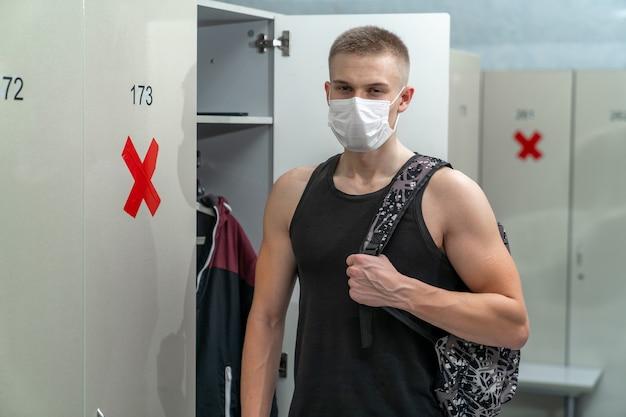 Un giovane uomo di corporatura atletica con una maschera medica sul viso in uno spogliatoio con armadi con etichette che ricordano la distanza sociale