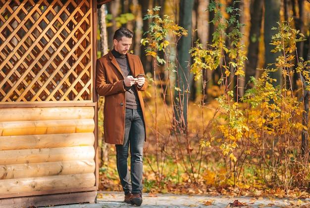 Giovane uomo in autunno parco all'aperto allargò le braccia