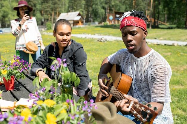 Giovane uomo in bandana seduto a tavola e cantando una canzone per gli amici nel paese