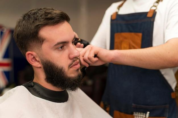 Giovane dal barbiere che si fa tagliare i capelli