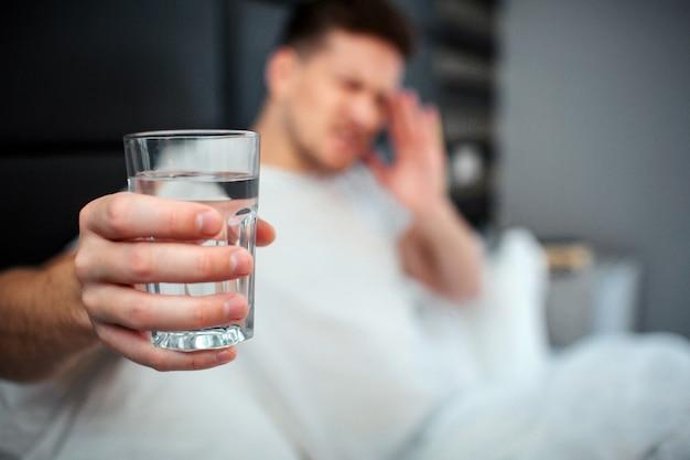 Giovane uomo a letto con in mano un bicchiere d'acqua, con mal di testa o postumi di una sbornia