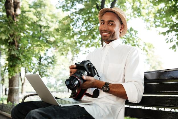 Giovane uomo su una panchina con laptop e fotocamera