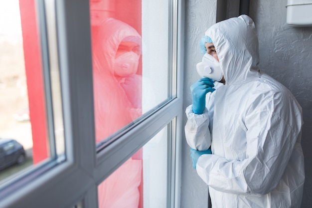 Il giovane in abbigliamento a rischio biologico resta isolato a casa per l'auto-quarantena. concept home quarantine, prevenzione covid-19.