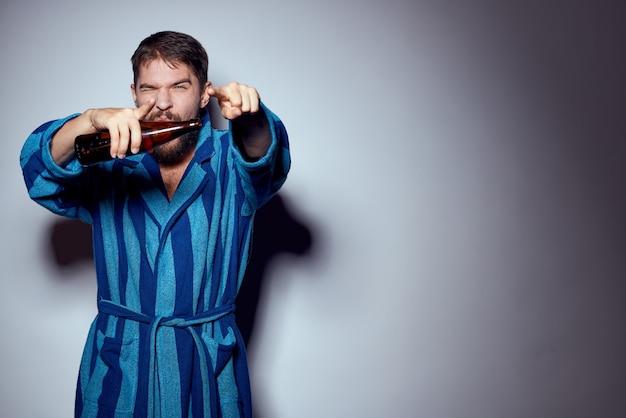 Giovane uomo in una veste blu isolato