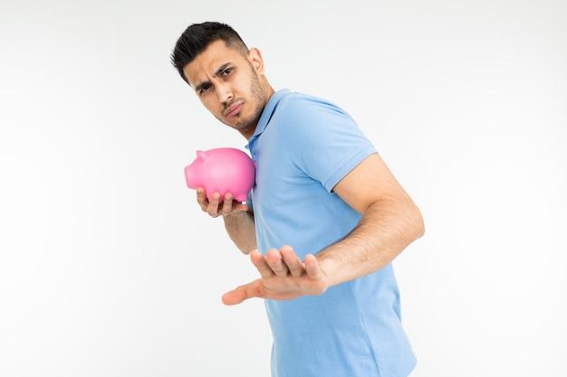 Il giovane in una maglietta blu tiene un porcellino salvadanaio e non è d'accordo mostrando il gesto di rifiuto su uno sfondo bianco studio