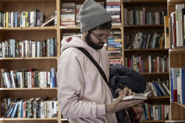 Giovane uomo in una libreria. bruna con gli occhiali e un cappello tiene un libro tra le mani. istruzione, scienza e conoscenza.