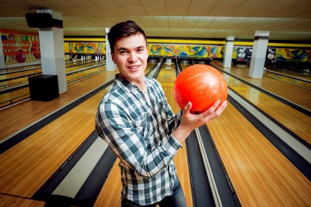 Giovane uomo al bowling con la palla.