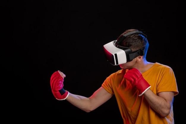 Giovane uomo boxe nella realtà virtuale con guanti da mma sulla superficie nera