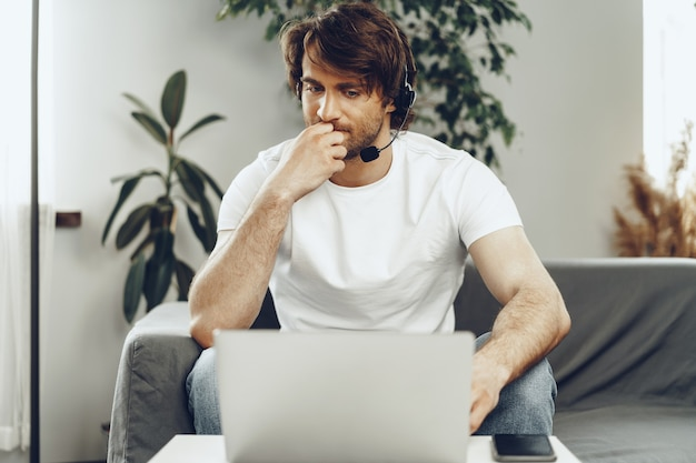 Uomo d'affari del giovane con la cuffia avricolare che lavora al computer portatile da casa