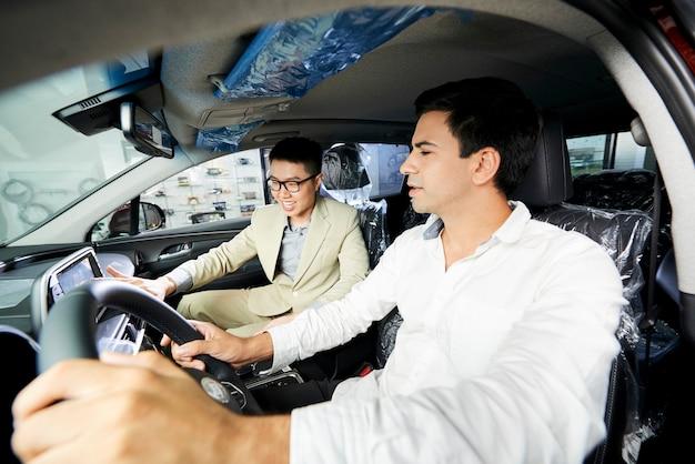 Giovane che compra una nuova auto, lui seduto nel salone dell'auto insieme al venditore asiatico e prova una nuova auto