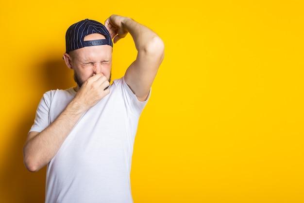 Giovane uomo in berretto e t-shirt con ascelle sudate e puzzolenti su sfondo giallo.