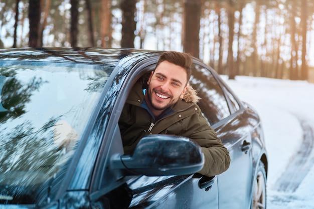 Giovane in auto strada invernale