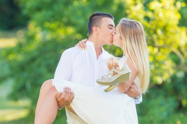 Giovane che porta la sua ragazza tra le braccia mentre si bacia nella natura in una giornata di sole... entrambi vestiti di bianco, tiene le scarpe in mano.