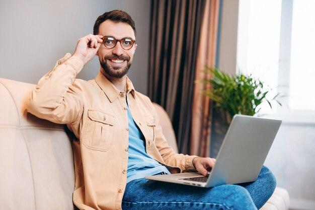 Giovane uomo in abiti casual sorride mostrando i suoi denti e ripara gli occhiali mentre è seduto sul divano con il computer portatile