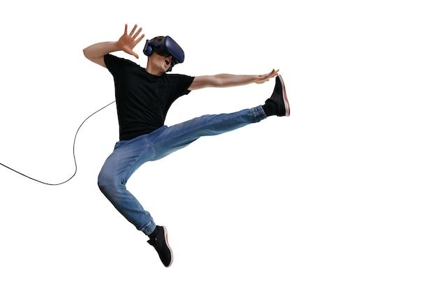 Giovane uomo in abiti casual utilizzando l'auricolare vr per giocare e immagina di essere un combattente. innovare la tecnologia di intrattenimento