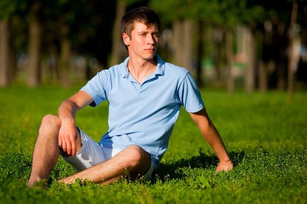 Giovane in abbigliamento casual che si siede sull'erba verde e che osserva da parte nel parco in giornata limpida estiva. libertà interiore e concetto di stile di vita felice