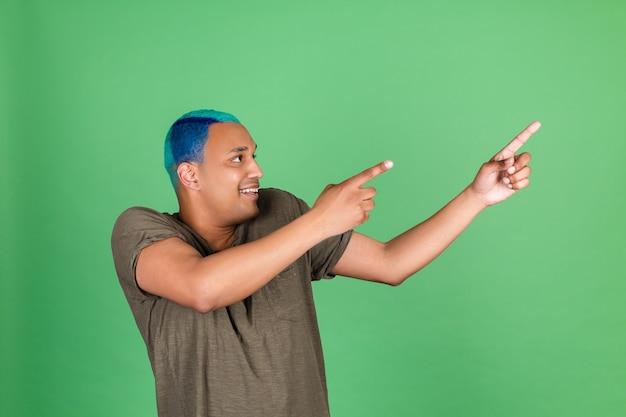 Giovane in casual sulla parete verde capelli blu allegro punto positivo dito a destra