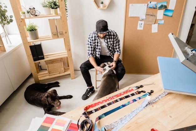 Giovane uomo in abbigliamento casual che indossa un colletto fatto a mano sul collo di uno dei suoi animali domestici mentre usciva con loro
