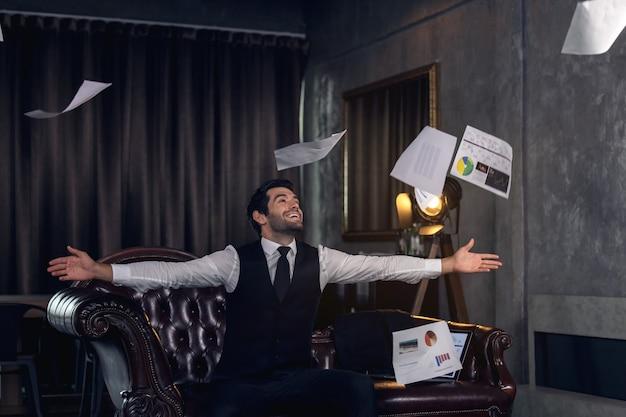 Giovane che celebra in ufficio, uomo d'affari che applaude alla sua scrivania