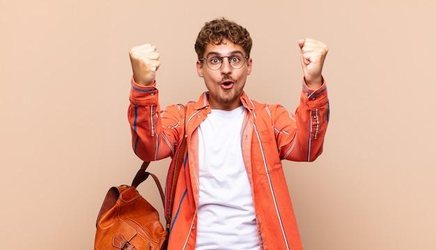 Giovane che celebra un incredibile successo come un vincitore, sembra eccitato e felice dicendo prendilo