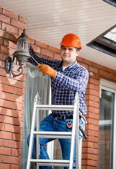 Giovane uomo che cambia lampadina alla lampada da esterno