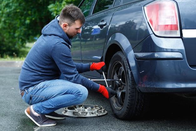 Giovane uomo che cambia gomma a terra sulla sua auto dopo un incidente stradale