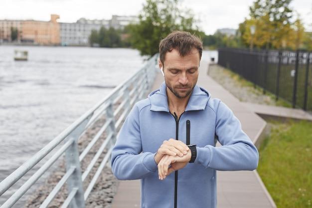 Giovane che controlla il suo polso sul braccialetto fitness durante il suo jogging nel parco