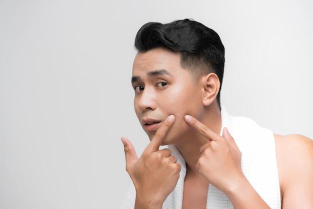 Giovane che controlla la sua pelle, concetto di cura della pelle maschile, trattamento dell'acne