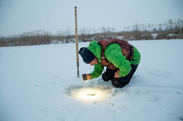 Il giovane controlla un buco in un lago ghiacciato su un pescatore invernale