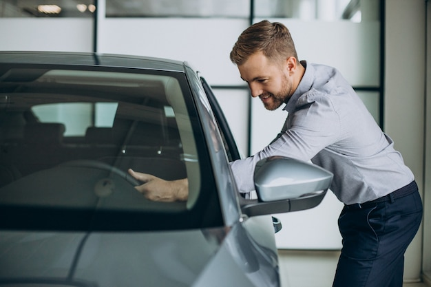 Giovane che sceglie un'auto in un salone di auto