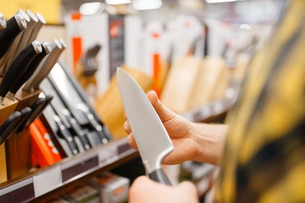 Giovane che sceglie coltello da cucina, negozio di casalinghi