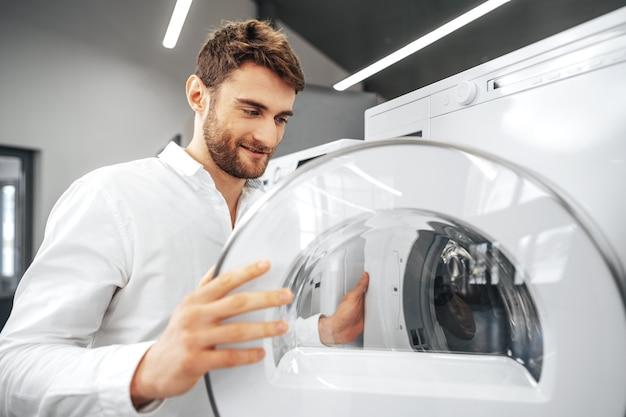 Giovane che sceglie la nuova lavatrice nel negozio di elettrodomestici