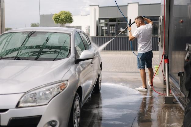 Giovane che pulisce la sua auto con un autolavaggio self-service con spruzzatore a getto