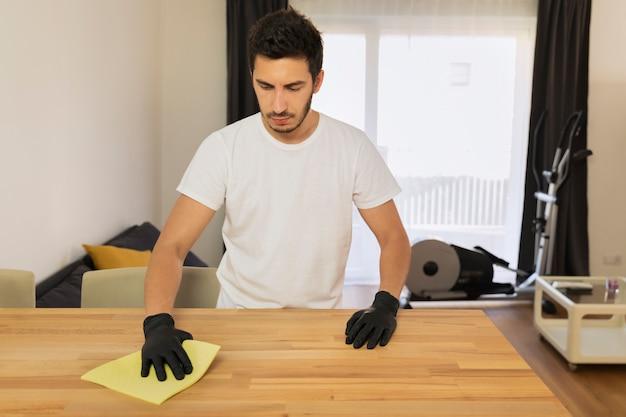 Un giovane pulisce a casa. il marito aiuta sua moglie nelle faccende domestiche.