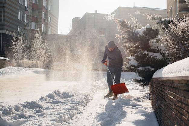 Un giovane spazza la neve davanti alla casa in una giornata di sole e gelo. pulire la strada dalla neve.