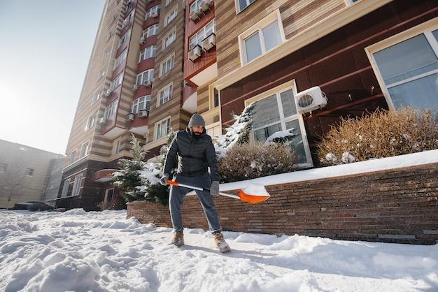 Un giovane spazza la neve davanti alla casa in una giornata soleggiata e gelida. pulire la strada dalla neve.